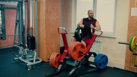 Homem atlético em um gym que trabalha em um simulador video estoque