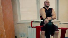 Homem atlético em um gym que trabalha em um simulador vídeos de arquivo