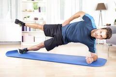 Homem atlético no entabuamento lateral com o um pé levantado imagem de stock