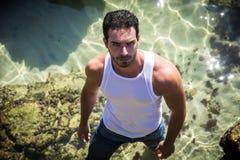 Homem atlético no mar ou no oceano por rochas, t-shirt molhado imagens de stock
