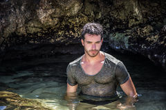 Homem atlético no mar ou no oceano por rochas, t-shirt molhado fotos de stock