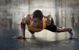 Homem atlético novo que faz impulso-UPS fotografia de stock