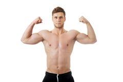 Homem atlético novo que mostra seus músculos fotografia de stock