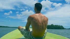 Homem atlético novo que senta-se na curva do barco e que levanta as mãos para apreciar a liberdade Indivíduo desportivo feliz que filme