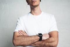 Homem atlético novo que veste o t-shirt branco vazio e o relógio esperto, fotografia de stock royalty free