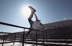 Homem atlético novo vestido no t-shirt branco, nas caneleiras pretas e no short azul fazendo o truque que salta sobre os trilhos fotografia de stock