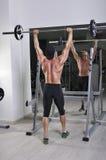 Homem atlético poderoso considerável que faz o exercício da imprensa do ombro do barbell fotos de stock