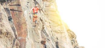 Homem atlético que clambing uma parede no por do sol - montanhista da rocha que executa em uma montanha da garganta que faz um sa foto de stock royalty free