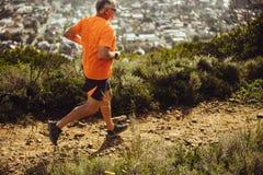 Homem atlético que corre em um monte imagens de stock