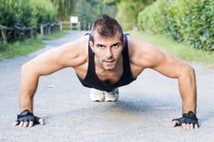 Homem atlético que faz a flexão de braço exterior. fotografia de stock royalty free