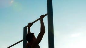 Homem atlético que pratica em barras desiguais, no estilo de vida ativo e no esporte, passatempo foto de stock royalty free