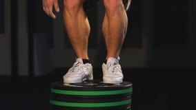 Homem atlético que salta no gym Exercício do treinamento de Crossfit O homem com exercícios despidos do torso salta no fundo escu vídeos de arquivo