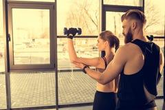 Homem atlético que treina a mulher desportiva nova com pesos no gym imagens de stock royalty free