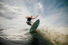 Homem atlético que wakesurfing na placa contra o céu nebuloso imagens de stock royalty free