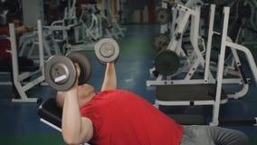 Homem atl?tico e atrativo que faz a imprensa de banco do peso no gym vídeos de arquivo