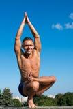 Homem atlético feliz que faz asanas da ioga no parque no dia ensolarado Imagem de Stock Royalty Free