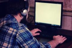 Homem atrás do computador com fones de ouvido Fotos de Stock Royalty Free