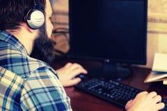 Homem atrás do computador com fones de ouvido Fotografia de Stock