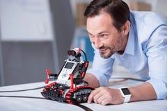 Homem atrativo de meia idade que lança um robô imagem de stock royalty free
