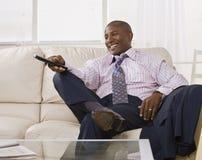 Homem atrativo do americano africano que presta atenção à tevê Fotos de Stock Royalty Free