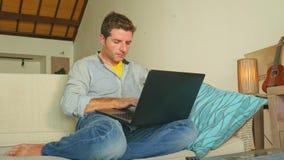 Homem atrativo e bem sucedido novo que trabalha da sala de visitas home que senta-se em trabalhos em rede do sofá no laptop feliz filme