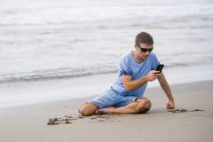 Homem atrativo e considerável em seu 30s que senta-se na areia relaxado na praia que ri na frente do mar que texting no pho móvel foto de stock