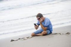 Homem atrativo e considerável em seu 30s que senta-se na areia relaxado na praia que ri na frente do mar que texting no pho móvel fotos de stock