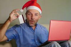 Homem atrativo e feliz novo no chapéu de Santa Klaus Christmas usando o laptop para comprar presentes e presentes do xmas em linh imagens de stock royalty free