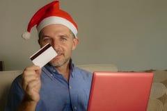 Homem atrativo e feliz novo no chapéu de Santa Klaus Christmas usando o laptop para comprar presentes e presentes do xmas em linh fotografia de stock