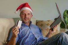 Homem atrativo e feliz novo no chapéu de Santa Klaus Christmas usando o laptop para comprar presentes e presentes do xmas em linh fotos de stock royalty free