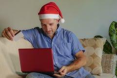 Homem atrativo e feliz novo no chapéu de Santa Klaus Christmas usando o laptop para comprar presentes e presentes do xmas em linh imagens de stock