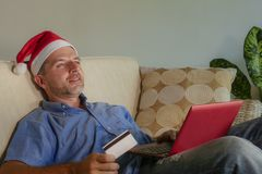Homem atrativo e feliz novo no chapéu de Santa Klaus Christmas usando o laptop para comprar presentes e presentes do xmas em linh foto de stock royalty free