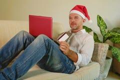 Homem atrativo e feliz novo no chapéu de Santa Klaus Christmas usando o laptop para comprar presentes e presentes do xmas em linh imagem de stock royalty free