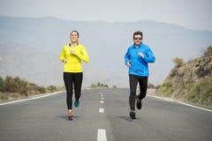 Homem atrativo e mulher dos pares do esporte que correm junto na paisagem da montanha da estrada asfaltada Imagens de Stock Royalty Free