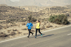 Homem atrativo e mulher dos pares do esporte que correm junto na paisagem da montanha da estrada asfaltada do deserto Fotos de Stock