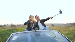 Homem atrativo e mulher que tomam o selfie ao sentar-se no cabriolet filme