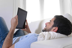 Homem atrativo feliz novo que usa a almofada ou a tabuleta digital que sentam-se no sofá Imagens de Stock Royalty Free