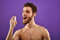 Homem atrativo impressionante que aplica o pulverizador fresco da respiração foto de stock royalty free