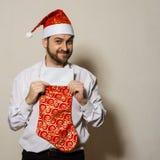 Homem atrativo no tampão do Natal, peúgas para presentes Fotografia de Stock