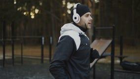 Homem atrativo nos fones de ouvido que fazem o exercício do aquecimento que prepara-se para movimentar-se quando música de escuta filme