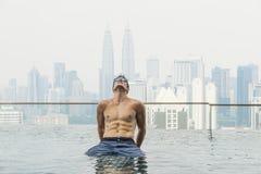 Homem atrativo novo na piscina no telhado no arranha-céus Fotografia de Stock Royalty Free