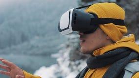 Homem atrativo novo no revestimento amarelo que aprecia auriculares dos vidros da realidade virtual ou jogo 3d fora em montanhas