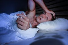 Homem atrativo novo preocupado agitado acordado na noite que encontra-se no sono de sofrimento desesperado da cama e forçado sem  fotos de stock