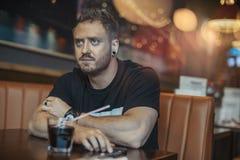 Homem atrativo novo que espera sua refeição no café fotos de stock