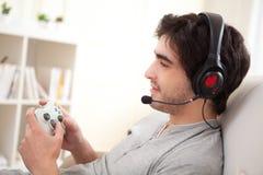 Homem atrativo novo que joga jogos de vídeo em um sofá Imagem de Stock Royalty Free