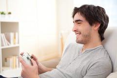 Homem atrativo novo que joga jogos de vídeo em um sofá Fotografia de Stock