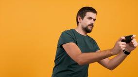 Homem atrativo novo que joga um jogo de vídeo em seu smartphone filme
