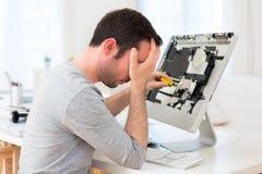 Homem atrativo novo que tenta reparar o computador fotografia de stock