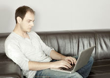 Homem atrativo que datilografa em seu portátil imagem de stock