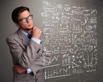 Homem atrativo que olha gráficos e símbolos do mercado de valores de ação Imagem de Stock Royalty Free